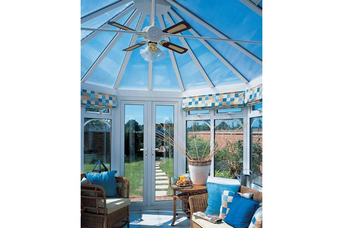 Internal view of conservatory with clear polycarbonate roof showing tie bar and fan