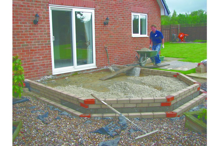 Aggregate is laid and compacted to a minimum of 100mm depth and a building screen of sand is laid on top.