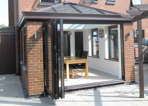 Brown Livin Room Conservatory with aluminium bifold doors